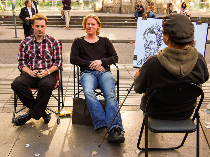 Caricaturist Artist Barcelona Caricature Drawing Fun Leisure Activity Lifestyles Rambla Real People Sitting SPAIN Street Togetherness The Tourist