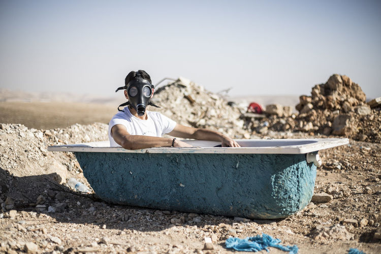 Portrait of young man wearing gas mask in bathtub against clear sky