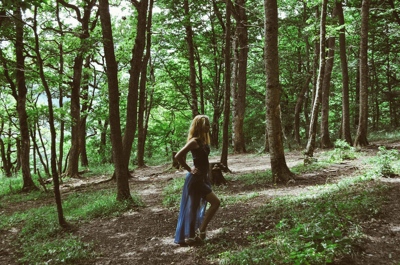 Full length of young standing woman in forest