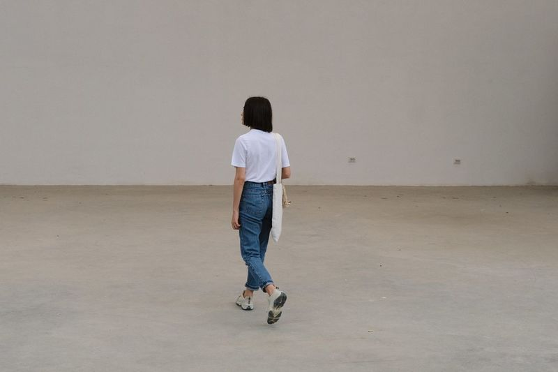 Rear view full length of woman walking on floor against wall