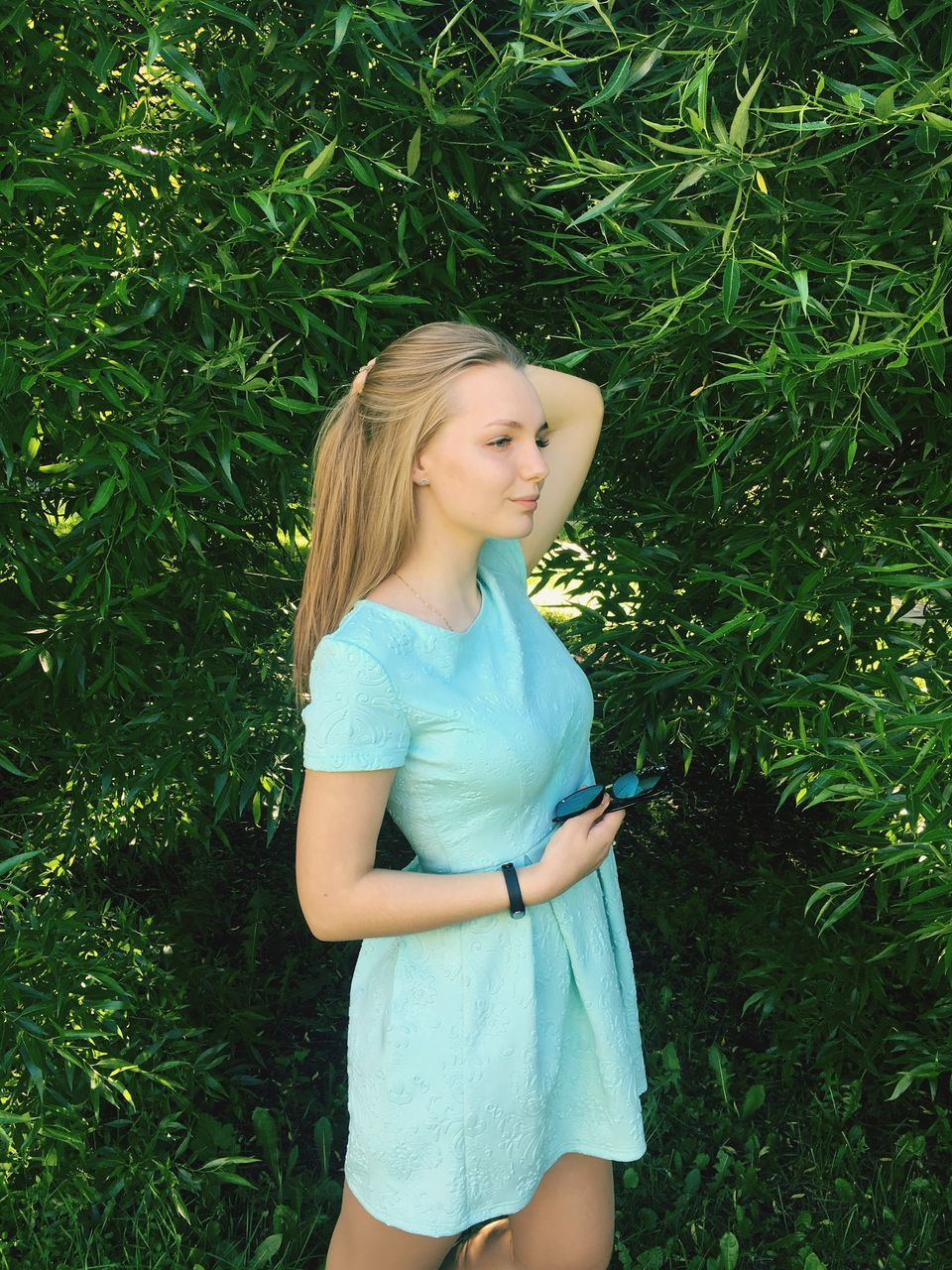 one person, real people, young adult, teenage girls, standing, casual clothing, grass, plant, long hair, young women, growth, green color, teenager, leisure activity, day, outdoors, nature, lifestyles, blond hair, tree, smiling, people
