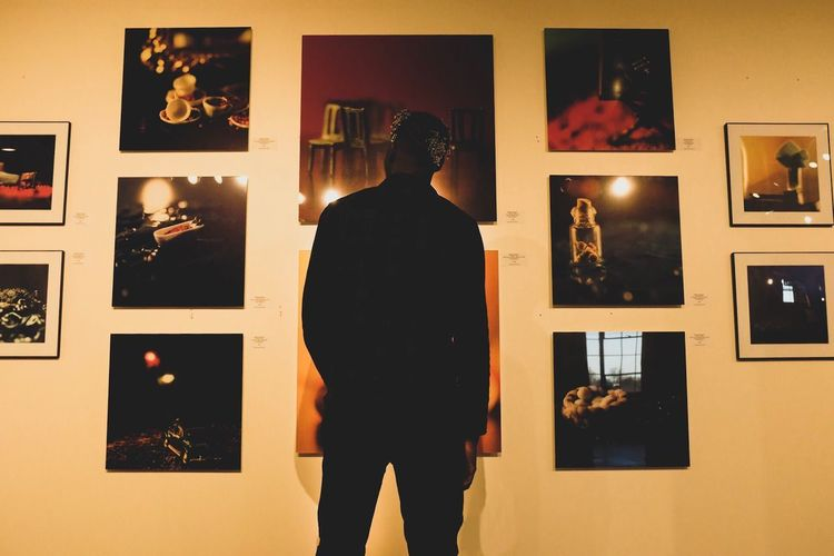 Rear view of man standing in illuminated room