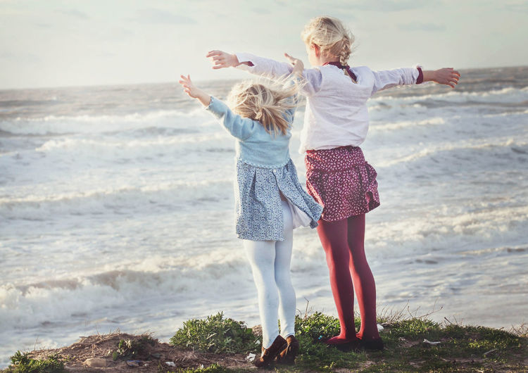 Rear view of sisters with arms outstretched standing on cliff against sea