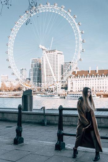 Woman sitting on ferris wheel against buildings in city
