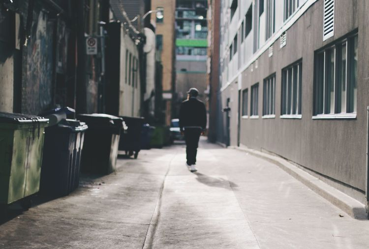 Man Walking In Empty Alley