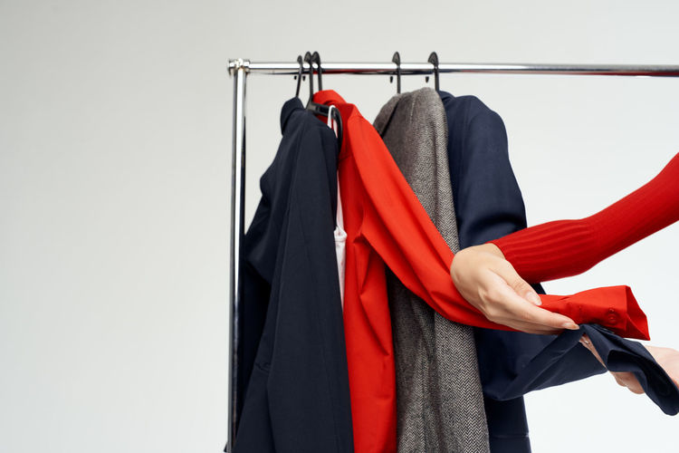 Red clothes hanging on rack against white background