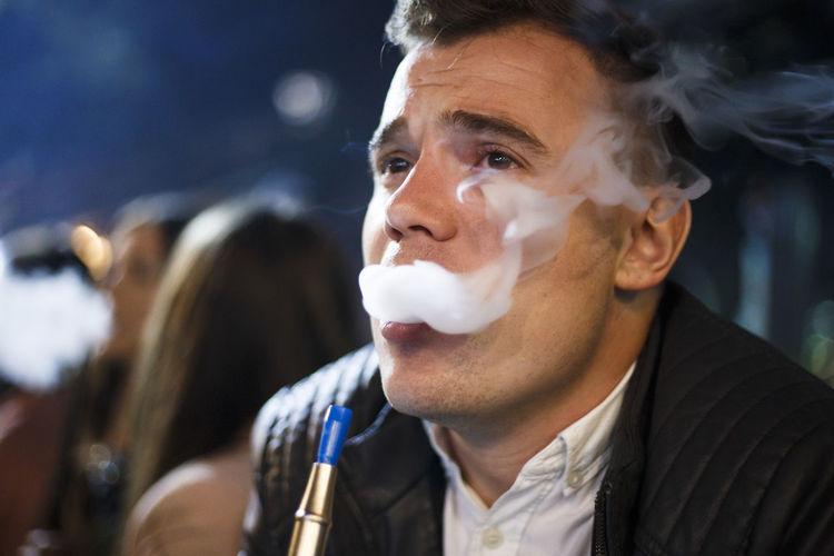 Close-up of man smoking hookah at night
