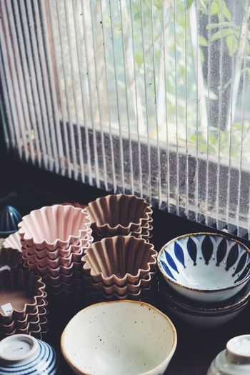High angle view of cupcake holders and bowls by window