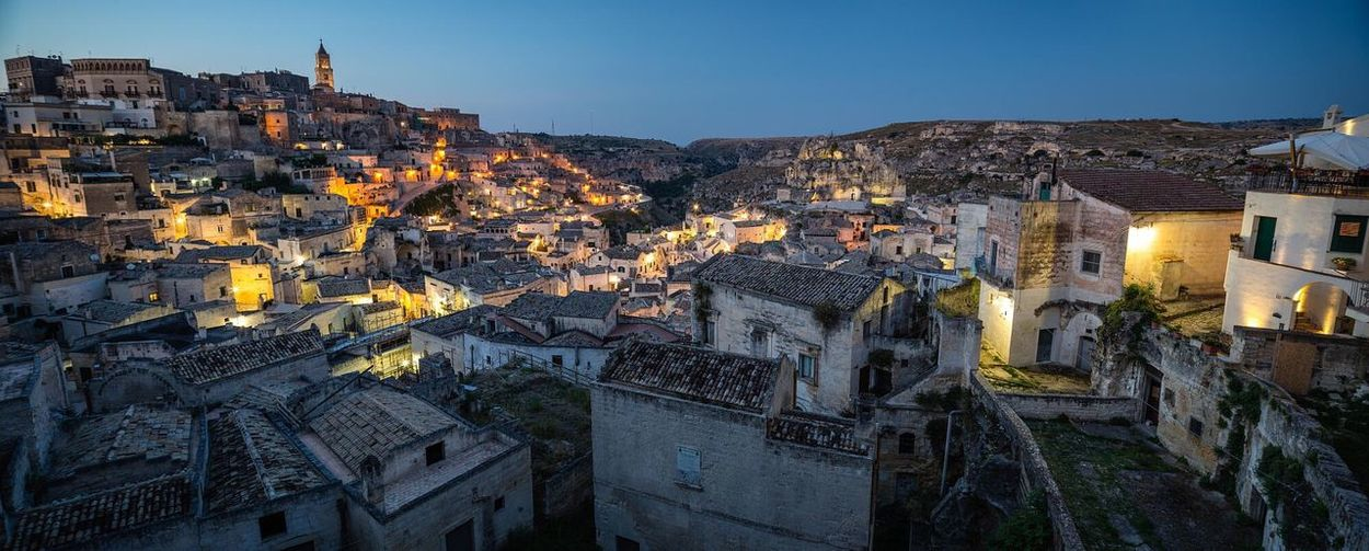 Panoramic view of illuminated cave dwellings at sassi di matera