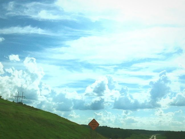 Hillside Road Sign Power Lines Clouds And Sky Cloudscape Sun And Sky Green Blue