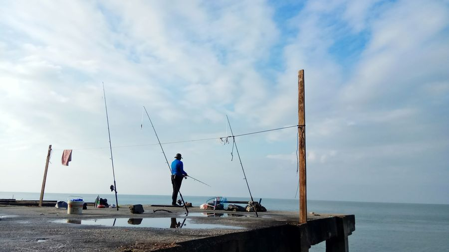 Rear view of man fishing in sea while standing on pier against cloudy sky