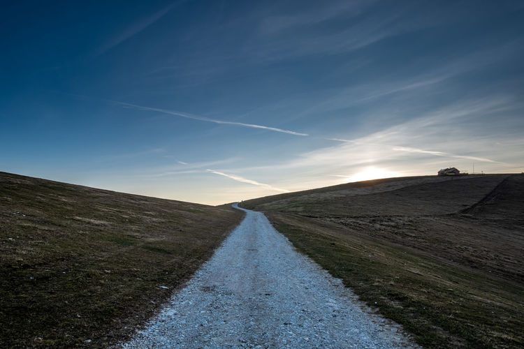 Road amidst land against sky during sunset