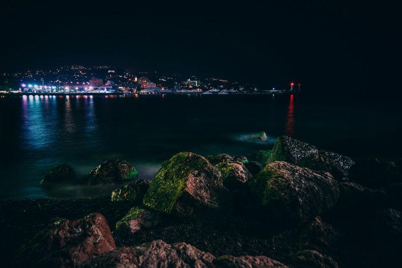 Illuminated city by sea at night
