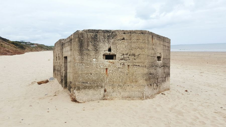Close-up of built structure on beach against sky