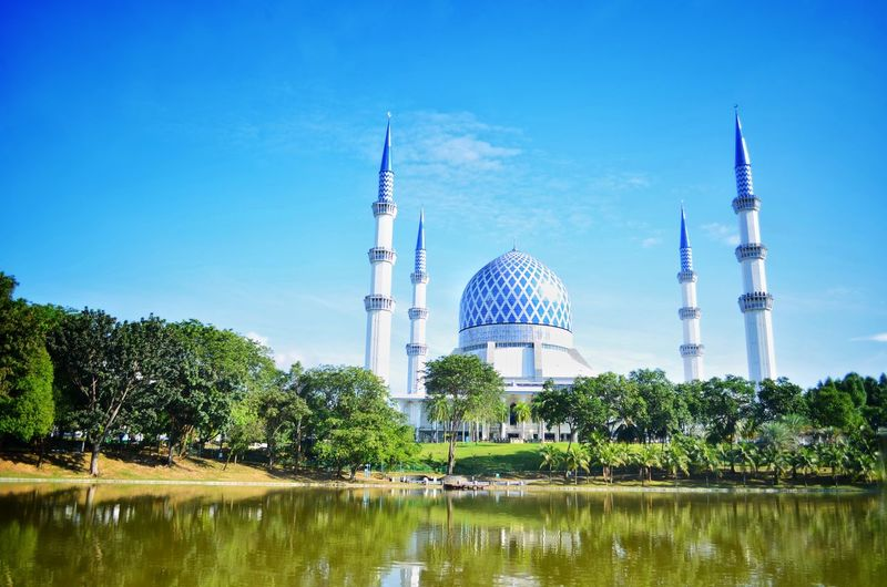 View of lake by building mosque against blue sky