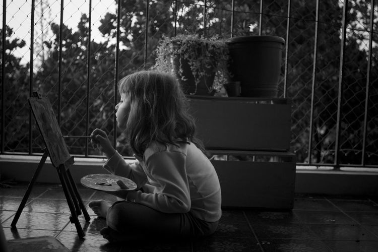 Girl painting on canvas in balcony