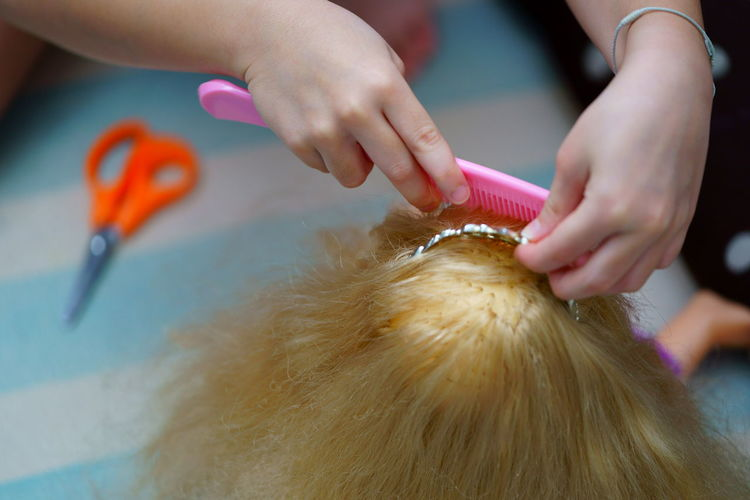 Cropped hands of girl combing doll hair at home