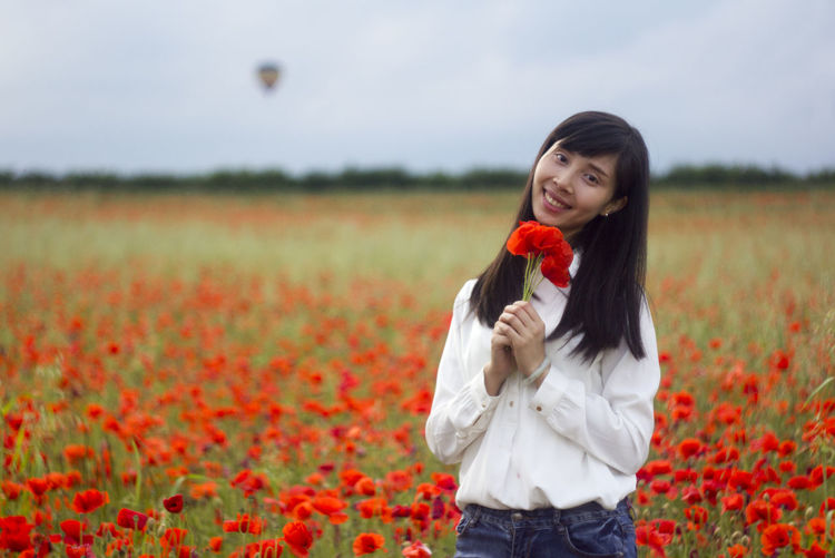 Woman Standing On Poppy Field