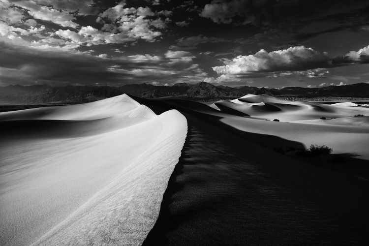 Scenic view of mesquite flat sand dunes against cloudy sky