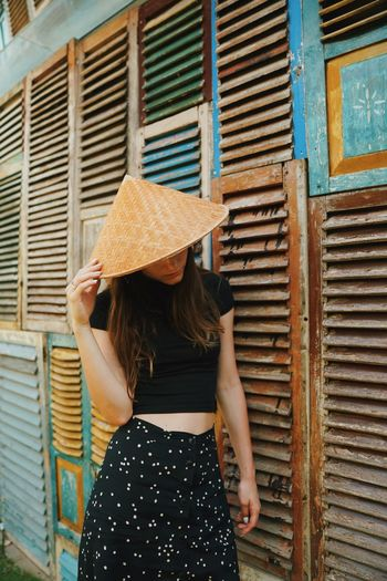 Woman wearing hat while standing by wooden wall