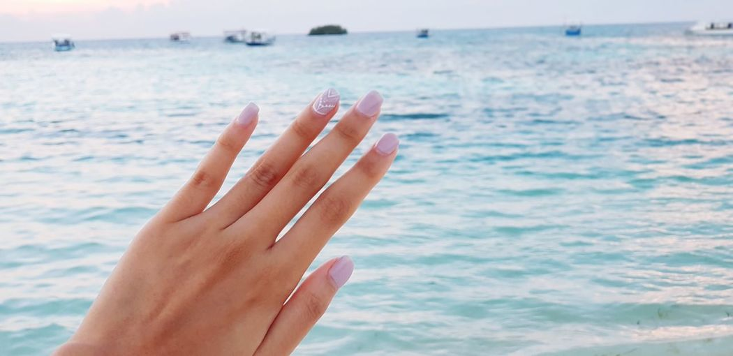 Cropped Image Of Woman Hand With Nail Polish On Fingernails Against Sea