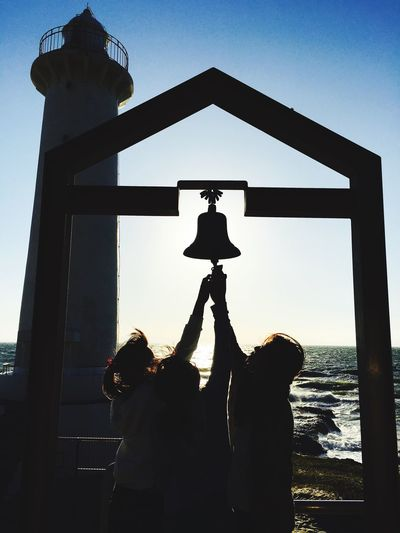 Girls holding bell by lighthouse against sky