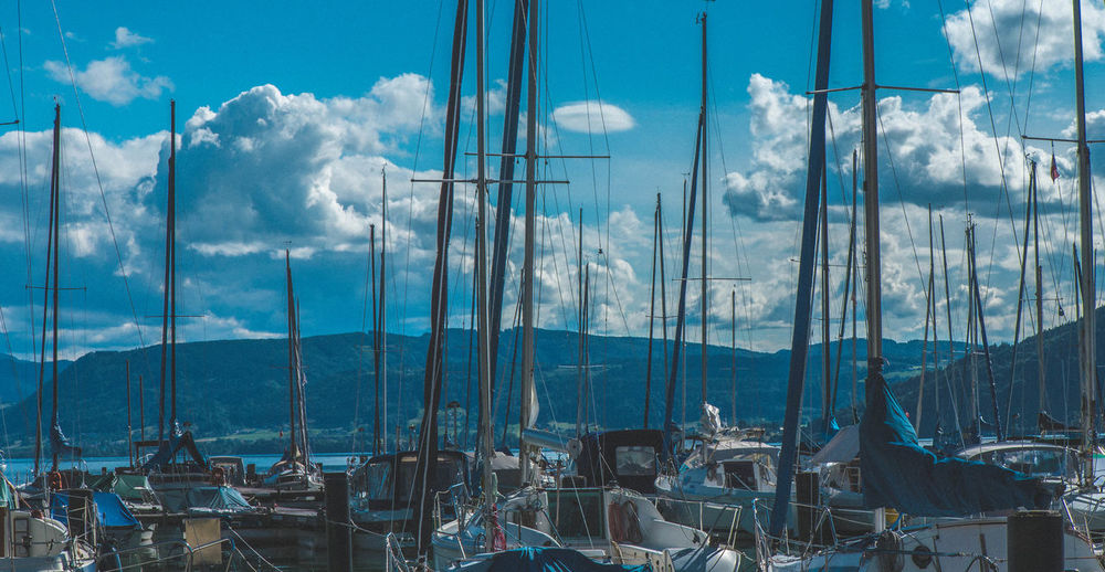 Boats Moored At Harbor Against Cloudy Sky