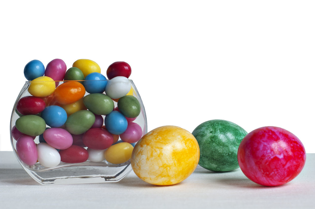 Close-Up Of Colorful Candies And Easter Egg Against White Background