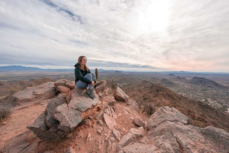 Full length of woman sitting on rock against sky