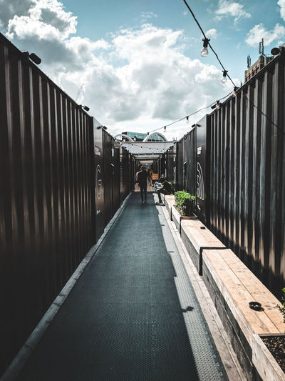 Boxpark Shoreditch Cityscape Sun Sunlight Travel Blue Sky City View  Travel Photography Teampixel Contrast London Shoreditch Shipping Containers Boxpark Lightroom Leading Lines Black Blue Sky City Sky Architecture Cloud - Sky Built Structure Footbridge Bridge - Man Made Structure vanishing point Diminishing Perspective The Way Forward Railing Boardwalk Pathway