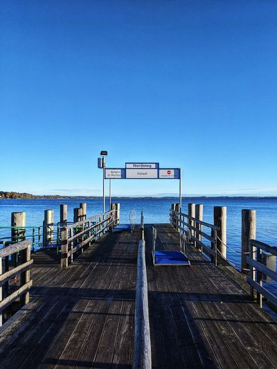 Empty pier on sea against clear blue sky