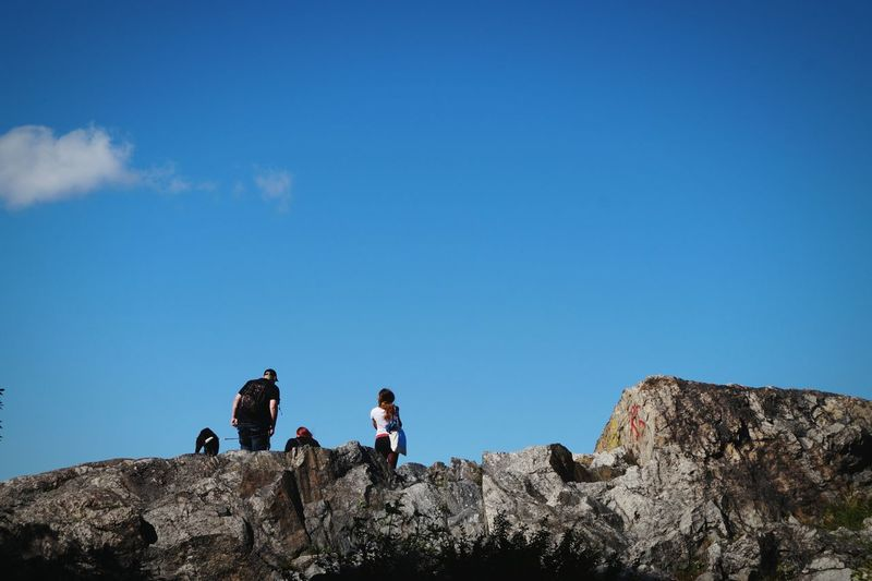 Low angle view of people on cliff against blue sky