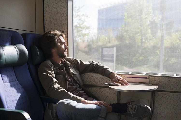 Man looking at camera while sitting on sofa at home