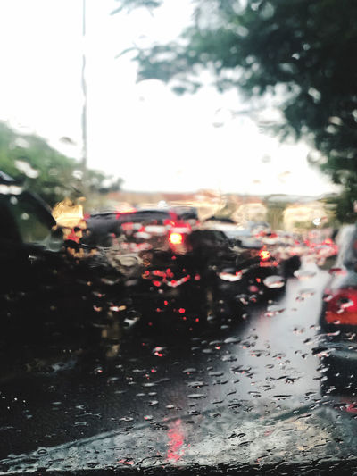 Cars on road seen through wet glass window during rainy season