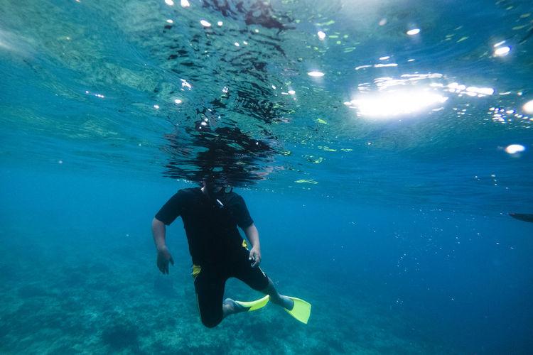 Man gesturing while snorkeling in sea