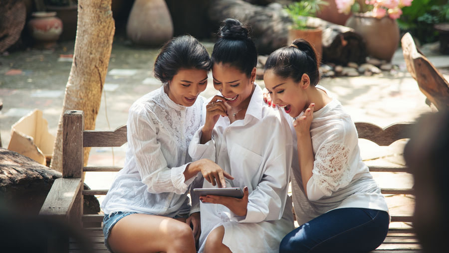 Cheerful females looking at digital tablet while sitting on bench