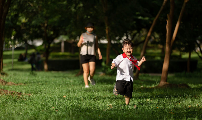 Full length of boy running on field with mother