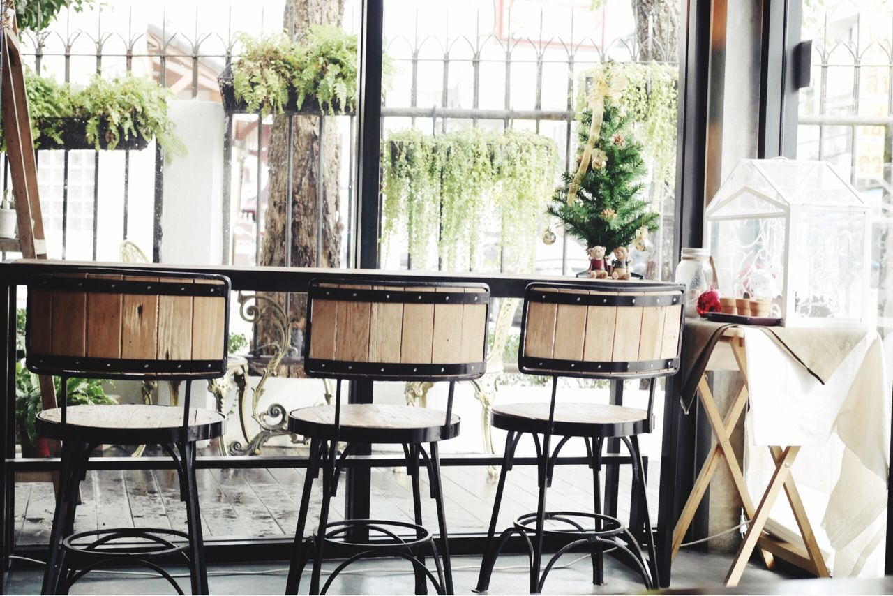 Empty Chairs Against Window Glass At Cafe