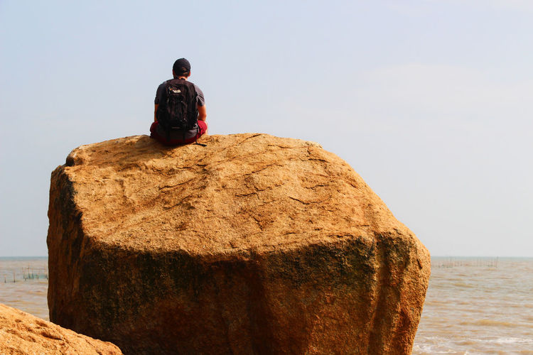 Rear View Of Backpacker Sitting On Rock Against Clear Sky