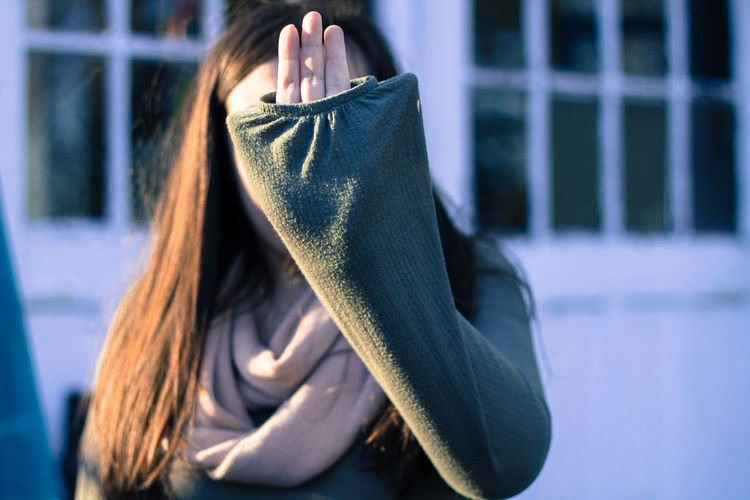 Close-up of woman covering face outdoors