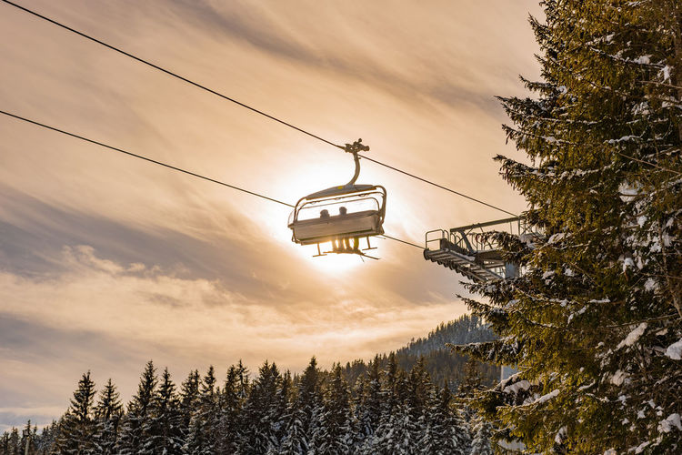Skiers going up the ski lift, chairlift against the orange sun. snowy mountains, ski slopes, trees