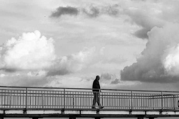 Rear view of man standing on bridge against sky