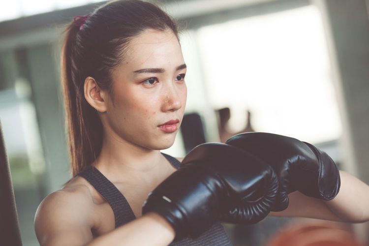 Close-up of woman wearing boxing gloves standing in gym