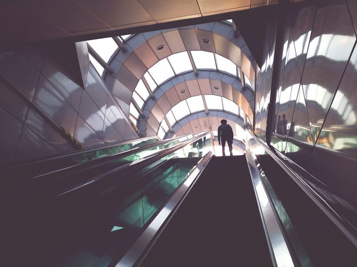 Low angle view of man standing on escalator in building
