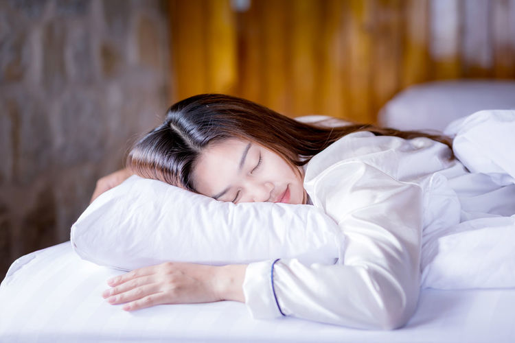 Beautiful Attractive Asian woman wearing Pajamas sleep close her eyes smile sleep and sweet dream on bed in bedroom in the morning feeling so relax and comfortable,Healthcare and Sleep Concept Adult Alone Asian  Attractive Beautiful Beauty Bed Bedroom Bright Comfortable Cozy Cute Dream Energy Face Female Fresh Girl Happy People Health Healthy Home Indoor Japanese  Joy Lady Lifestyles Lying Morning Nap People person Pillow Relax Relaxation Rest Resting Room Satisfaction Sleep Slim Smile Sweet Thai Time White Window Woman Young