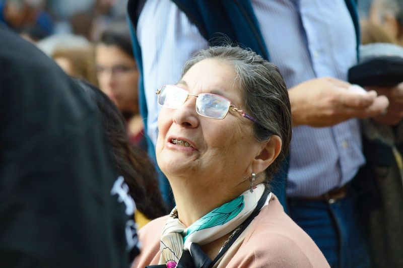 Close-up of senior woman amidst crowd