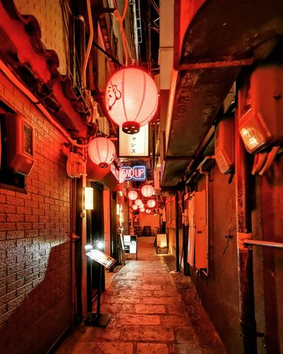 Illuminated lanterns hanging amidst buildings in city at night
