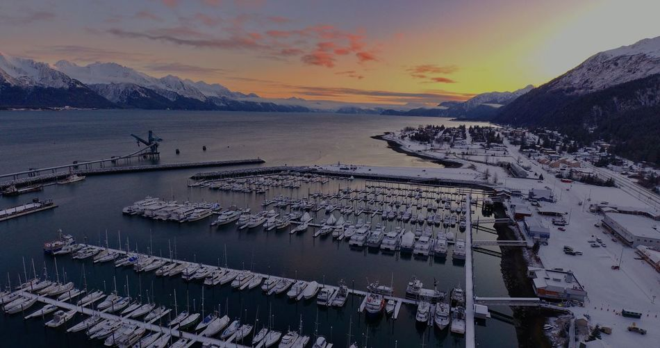 Aerial view of sea by snowcapped mountains against sky during sunset