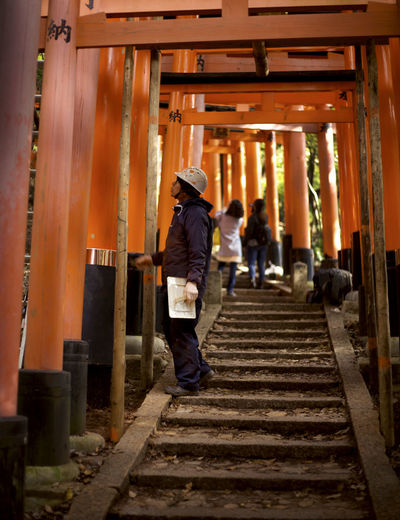Japan Japanese  Orange Shrine Travelling Working Workman Adult Architectural Column Architecture Building Exterior Built Structure Casual Clothing Culture Direction Full Length Hat Helmet Inari Men Outdoors People Place Of Worship Real People Religion Sky Staircase The Way Forward Tourism Travel Travel Destinations Walking Wood - Material