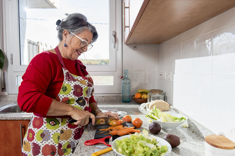 Woman standing by food in kitchen